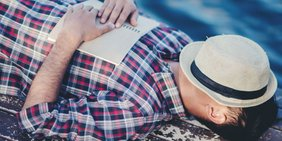 Mann liegt entspannt in der Sonne und geniest das Leben