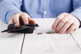 Mann hält leere Geldbörse in der Hand