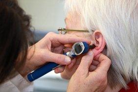 Mediziner untersucht das Ohr einer grauhaarigen Dame.
