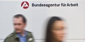 Ein Mann und eine Frau vor dem Logo der Agentur für Arbeit
