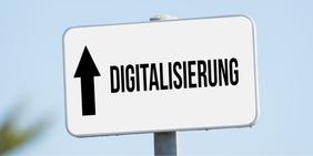 """Straßenschild mit der Aufschrift """"Digitalisierung"""" und einem Pfeil der nach oben zeigt"""
