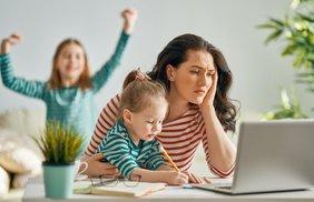 Gestresste Mutter im Homeoffice mit zwei Kindern
