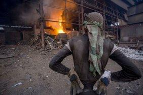 Arbeiter steht vor heruntergekommener Fabrik ohne richtiger Schutzkleidung