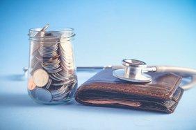 Glaß voller Münzen, Stethoskop liegt horchend auf einem Portmonee