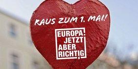 Rotes Herz mit Schrift Raus zum 1. Mai und Motto Europa! Jetzt aber Richtig!