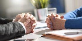 Zwei Personen am Schreibtisch gegenüber sitzend, nur die Hände sind sichtbar.