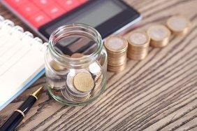 Spardose an der sich Geldstapelt, ein Tschenrechner sowie Notizblock