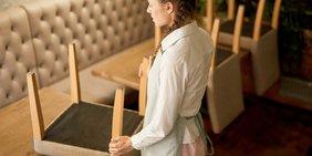 Frau (Kleidung einer Bedienung in Restaurant) stellt in leerer Restaurant-Umgebung Stühle auf Tische