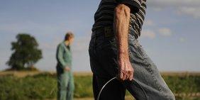 Älterer Mann auf dem Feld trägt einen Eimer