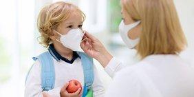 Frau mit Kleinkind (Kindergartenalter), beide mit Mund - Nasen - Masken. Kind hält einen Apfel in der Hand