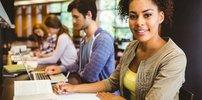 Junge Menschen arbeiten mit Buch und Laptop