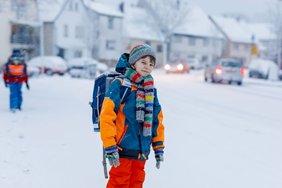 Kind im Schneeanzug auf dem weg zur Schule