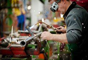 Metallarbeiter/Handwerker schweißt an Werkbank