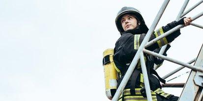 Junge Feuerwehrfrau auf der Leiter, blickt zurück