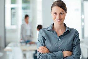 Frau steht Selbstbewust und zufrieden im Büro
