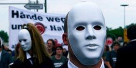 Maskierte Personen bei einer Demonstration