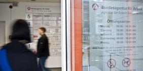 Menschen am Eingang einer Agentur für Arbeit