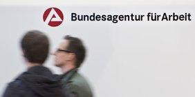 Zwei Männer vor einem Schild Arbeitsagentur