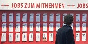 Ein Mann steht vor einer Pinnwand mit Jobangeboten.