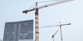 Zwei Baukräne und die Spitze eines Gebäude-Neubaus vor grauem Himmel
