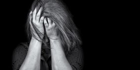 Schwarz-weiß-bild einer Frau die sich verzweifelt an den Kopf greift