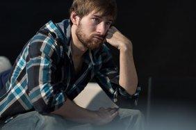 Junger  arbeitsloser Mann sitzt auf dem Sofa